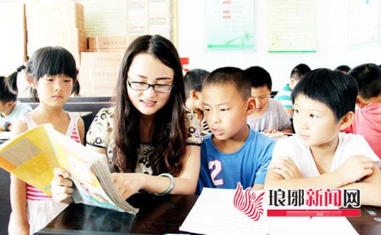 临沭县青云镇前齐庄村的大学生村官孙丽正在为村里的留守儿童辅导功课图片