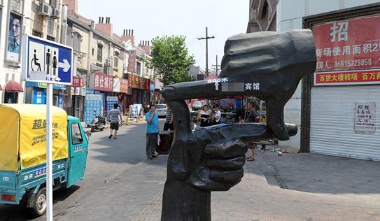 """青岛中山路上的标志性雕塑""""取景""""被商家贴上了塑料广告"""