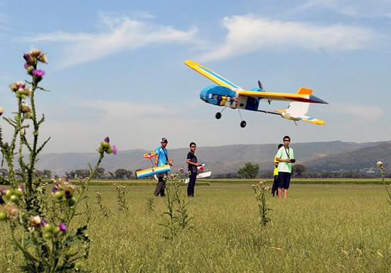 8月10日,在呼和浩特市航模飞行训练场,参加考试的航模飞行爱好者操控一架航模飞机掠草地飞行。   当日,内蒙古呼和浩特市航空航海车辆模型协会开展遥控航空模型飞行员执照考核工作,5名航模飞行爱好者先后顺利通过相应级别的理论和现场飞行考试,将获得由中国航空运动协会颁发的遥控航空模型飞行员执照。新华社发(王正 摄)