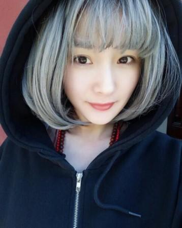 照片中她对镜头甜笑,抢眼的是头发已经染成了白色偏绿,完全看不出杨幂