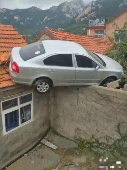 青岛一司机倒车 冲上村民屋顶