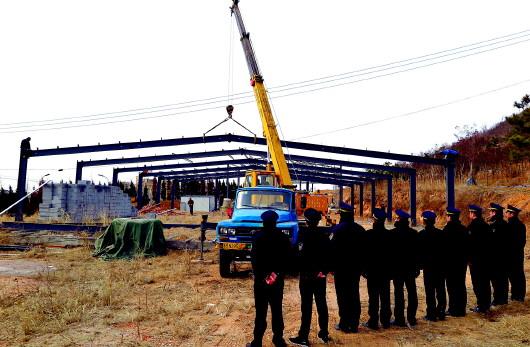 违建拆除现场,在大型吊车的帮助下,工人们逐一拆除钢结构。   17日上午,李沧区天水路和合川路路口拉起了警戒线,两辆大型吊车和十几名工人正在路边上坡处的空地上忙碌着。记者看到,眼前的空地上有两处大型的钢结构厂房,周围荒草丛生,工人爬到钢结构厂房顶部,拆卸螺丝后,用吊车将厂房部件小心翼翼堆放到一边。这处厂房没有前期规划审批手续,属于违法建筑。现场执法人员介绍,建造厂房的当事人原本是租用这块空地临时存放钢管等建材,去年4月份,他们巡查发现此处正在平整场地,有建设厂房地基的迹象。   执法人员加强巡查力