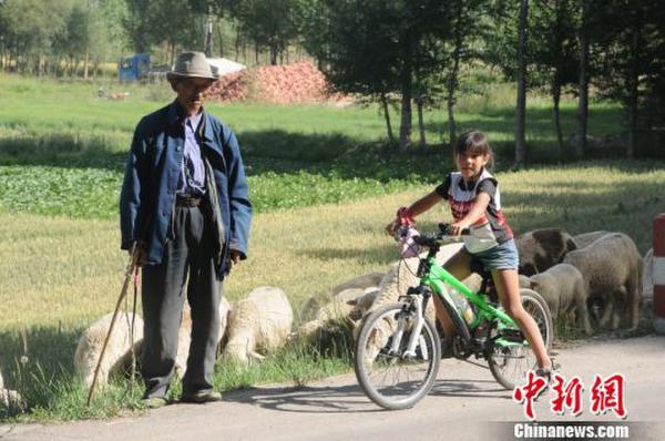 图为陈萱2009年骑行丝路途中和牧羊老人合影。 陈守忠提供 摄