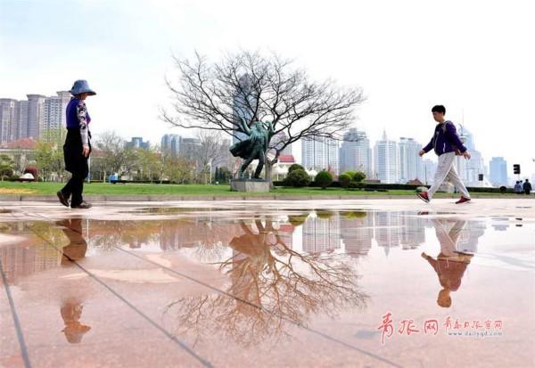 雨后,五四广场上存留的水洼如镜子一样