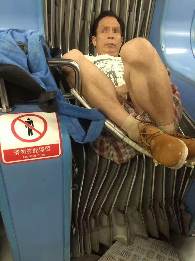 如图所示,轻轨车厢里,一名中年男子卷起双腿直接睡上车厢连接带,毫不