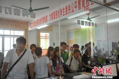 资料图:2017年8月,学生和家长在广西大化县教育局资助办申请助学贷款。 洪坚鹏 摄