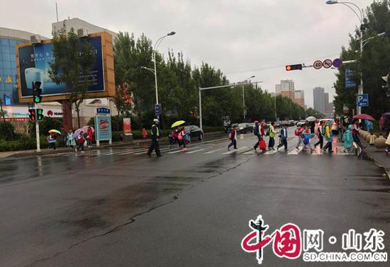 """滨州交警开发区大队:雨天""""护学岗""""上的浇警为学生撑起""""安全伞"""""""