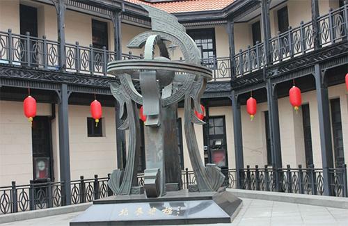 """1""""北辰建极""""的主题雕塑,主体为浑仪形象的变体,四龙托起天球,球上标示出北极星的位置,下方是黑色方形大理石基座,与上方的天球遥相呼应,象征中国传统文化中的""""天圆地方""""的宇宙观,雕塑中的""""北极星""""一语双关。"""